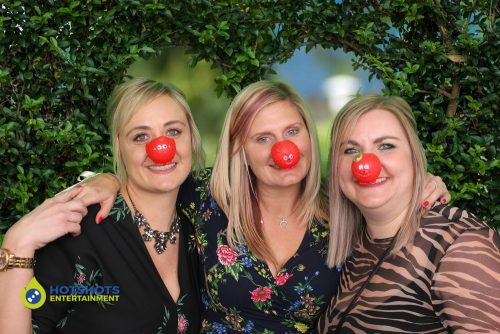 Great fun in the photo booth and with their children in need noses on.