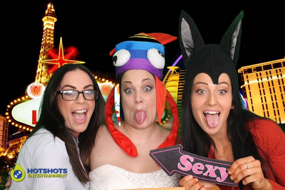 Bride having fun with her guests at a wedding photo booth hire, with funny props and green screen technology, in Vegas.