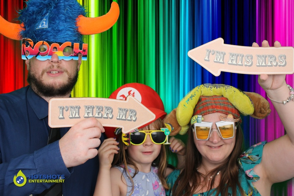 Wedding guests having fun in the photo booth with a rainbow background