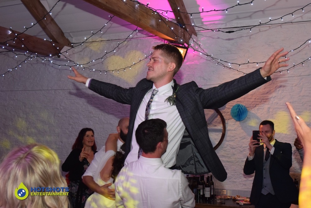 Groom being lifted in the air at his wedding disco on the dance floor