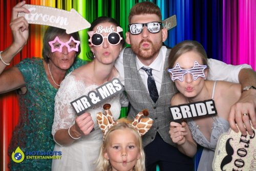 Bride and groom with bridesmaid having fun in the photo booth.