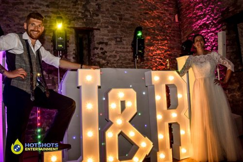 Bride and Groom with their light up letters, look great with the platinum disco at Priston Mill.