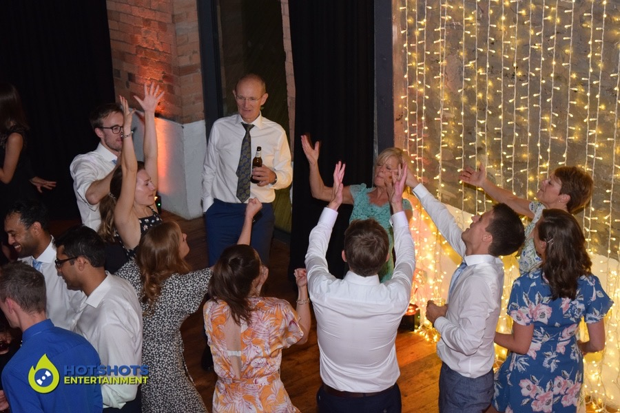Wedding guests chucking their hands in the air to a classic song at a wedding in Bristol