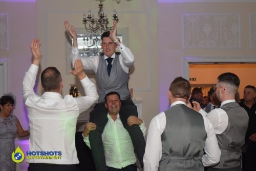 Groom being picked up and dancing around